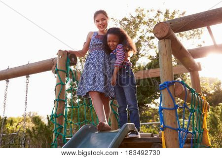 Two Girls Playing Outdoors At Home On Garden Slide