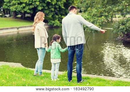family, parenthood, leisure and people concept - mother, father and little girl walking in summer park near pond