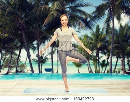 fitness, sport, people and healthy lifestyle concept - woman making yoga in tree pose on mat over hotel resort pool on tropical beach background