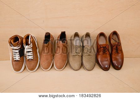 Row of Men's shoes and wooden background
