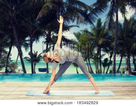 fitness, sport, people and healthy lifestyle concept - woman making yoga triangle pose on mat over hotel resort pool on tropical beach background