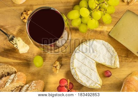 An overhead photo of a glass of red wine with a selection of cheeses, bread, and grapes