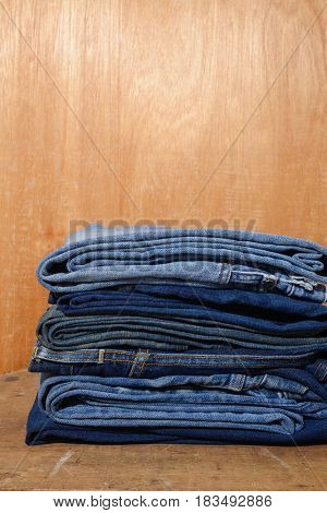 jeans trouser stacked on wooden background,