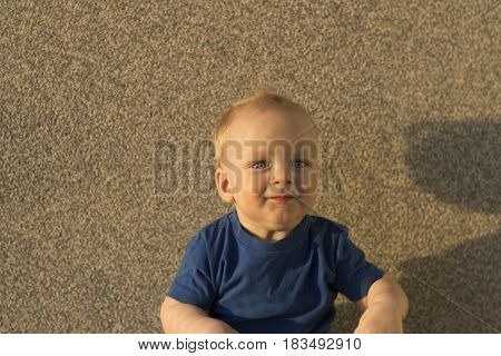 Satisfied Baby Boy Against The Background Of A Concrete Wall. Infant Kid With Unusual Shadows On His