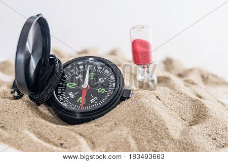 Sandglass, Dollar And Compass On Sand Isolated On White. Summer Concept