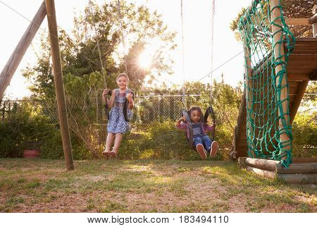 Two Girls Playing Outdoors At Home On Garden Swings