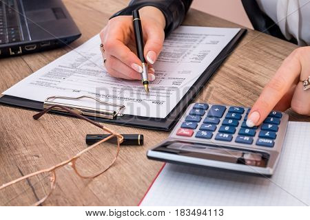 Woman filing individual income tax form 1040 with calculator. close up.
