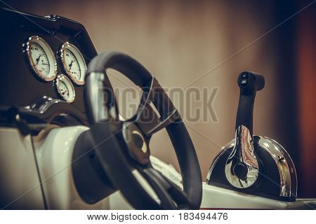 Close up shot of a lever and the steering wheel on a luxury boat.