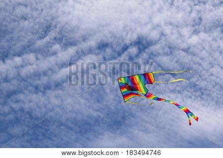 Rainbow kite flying flies fly above Australian beach against a blue clouded sky Summer days
