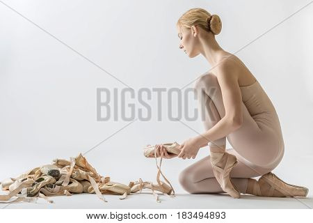 Blonde ballet dancer with closed eyes sits on the floor and holds a pointe shoe on the light background in the studio. She wears a beige dance wear. Next to her there is a pile of ballet shoes.