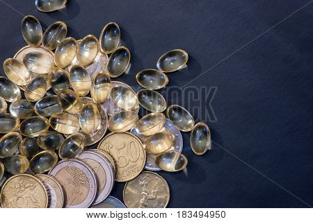omega 3 yellow pills with euro coin isolated on black
