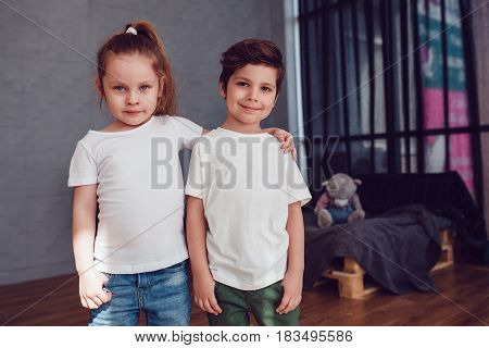 Two children in blank white t-shirt are hugging each other in studio. Mock up.