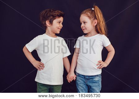 Two children in blank white t-shirts stand holding hands on black background.
