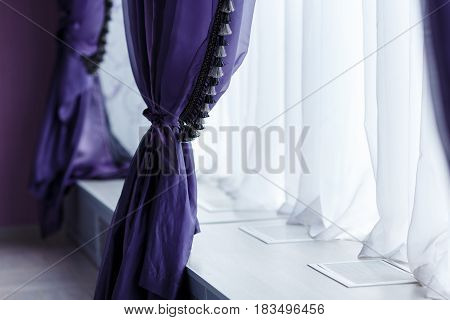 Purple curtains along window with a wide window sill. Day light