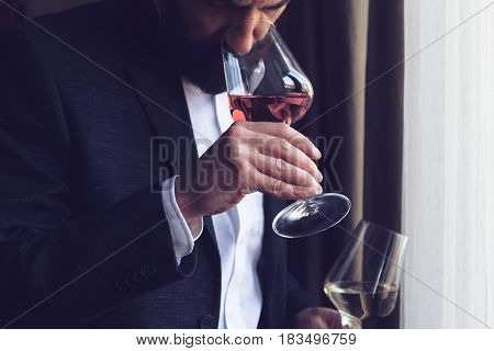horizontal close up of a Caucasian man with beard black suit and white shirt tasting a glass of rose wine at an event by the window natural light
