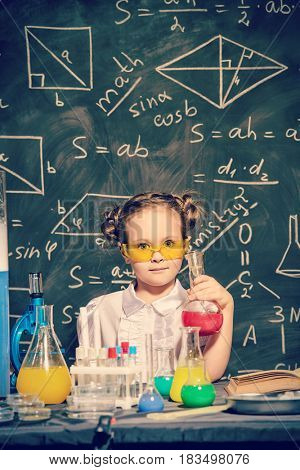 Cute little girl making experiments in the scientific laboratory. Educational concept. Early development of children.
