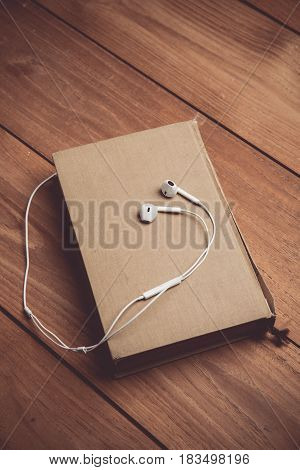 Vintage tone of a Bible with headphones. Hearing the voice of God concept.