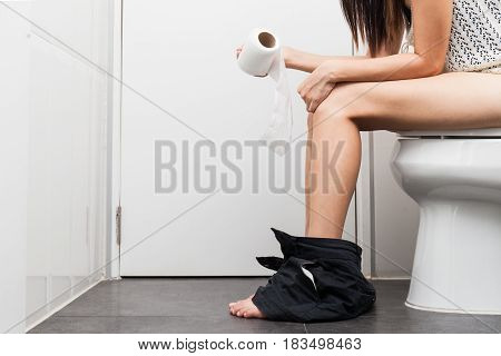 Using toilet. A young woman uses a toilet with a roll of toilet paper in her hand.
