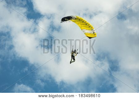 Pribram CZE - August 19 2016. Yellow paraglider flying against the cloudy sky in Pribram airport Czech Republic