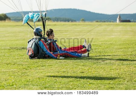 Pribram CZE - August 19 2016. Tandem red paraglider landing on grass in Pribram airport Czech Republic