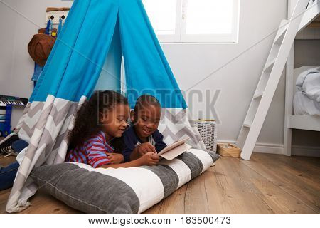 Two Children Lying In Tent In Playroom With Digital Tablet