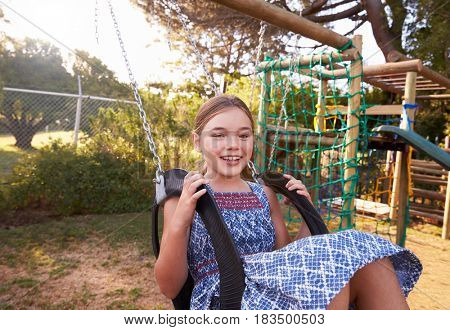 Girl Playing Outdoors At Home On Garden Swing