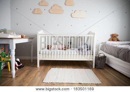 Side View Of Baby Girl Sleeping In Nursery Cot