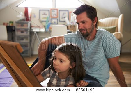 Father And Daughter Drawing On Chalkboard In Playroom