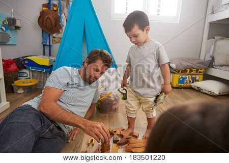 Father And Children Playing With Building Blocks In Bedroom