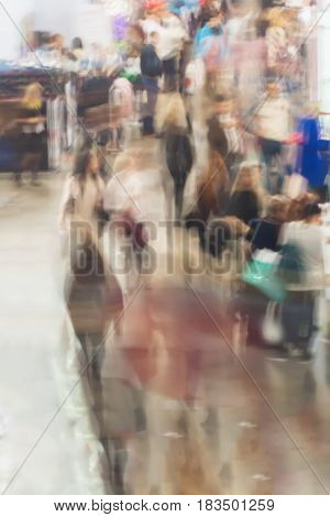 Abstract people walking in exhibition - trade fair show, defocused motion blurred background , backdrop