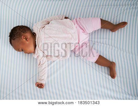 Overhead Shot Of Baby Girl Sleeping In Nursery Cot