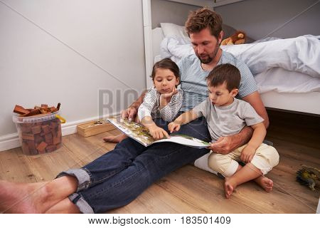 Father Reading Story To Children In Their Bedroom