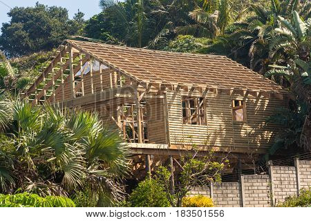 House home structure halfway wood log construction in tropical coastline environmemt landscape.