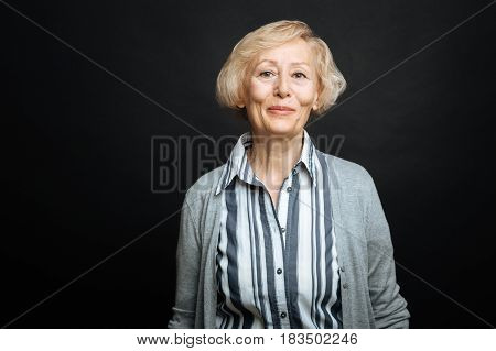 Sharing positivity with you. Cheerful pleasant old woman smiling and expressing positivity while standing isolated against black background
