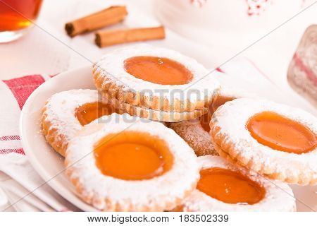 Teatime biscuits with jam on white dish.
