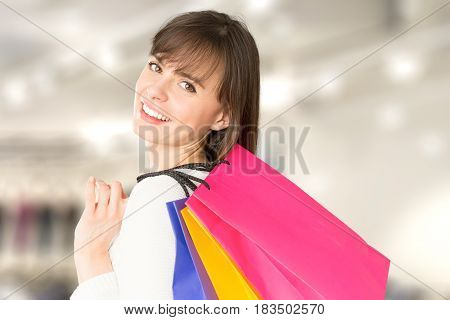 Beautiful and smiling young woman doing shopping in the mall. On the shoulder is holding a bag of groceries.