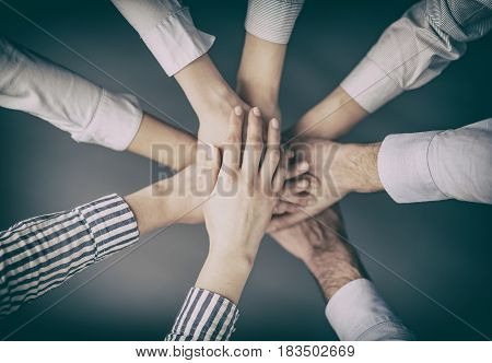 Business people hands stacked in a pile. A symbol of teamwork and trust.