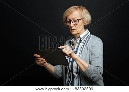 Becoming familiar with modern technologies. Concentrated skilled senior woman demonstrating interest and using gadget while standing isolated in black background
