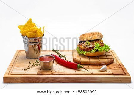 Cheeseburger with potato chips in a bucket ketchup and chili on a wooden board