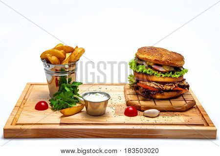 Cheeseburger with potatoes in Selyanski in a bucket sauce on a wooden board