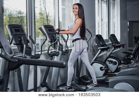 Training in the gym. Fitness girl posing and showing her figure. Fitness coach rests on the Step machine after training. Sport model posing in a sports suit