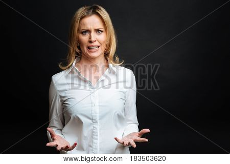 Stop provoking me. Angry overwhelmed mature woman expressing annoyance while gesticulating wildly and standing isolated in black background