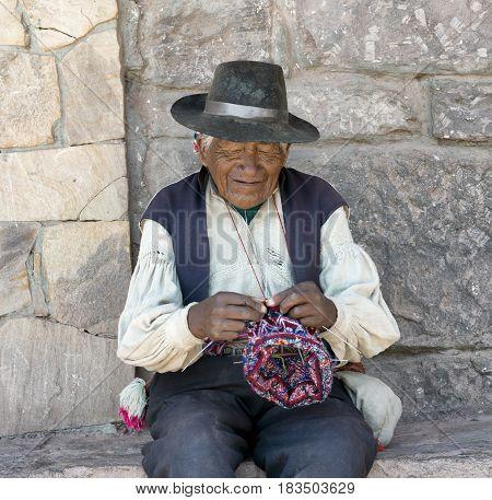 Peruvian native man knitting a hat. October 17 2012 - Taquile Island Lake Titicaca Peru