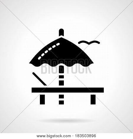Monochrome symbol of deckchair with sun umbrella. Sunbathe and summer leisure concept. Symbolic black glyph style vector icon.