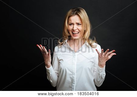 Stop provoking my indignation. Furious expressive annoyed woman expressing resentment and yelling while gesticulating wildly and standing isolated in black background