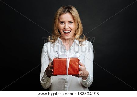 Enjoying my happy day. Glad positive smiling woman expressing joy and holding gift box while standing isolated in black background