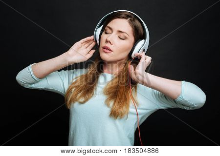 Time for meditation. Delighted young peaceful woman expressing peacefulness and using headphones while listening to the music and standing isolated in black background