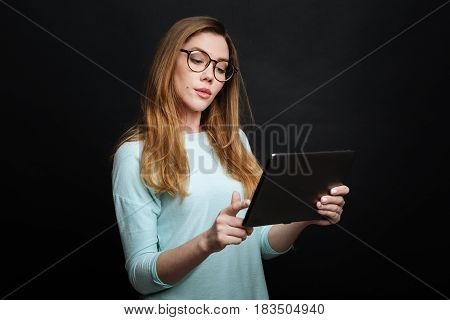 Exploring world of technology . Concentrated smart attractive woman expressing delight and using tablet while standing isolated in black background