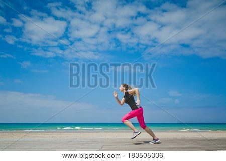 Healthy woman running on the beach, girl doing sport outdoor, happy female exercising, freedom, vacation, fitness and heath care concept