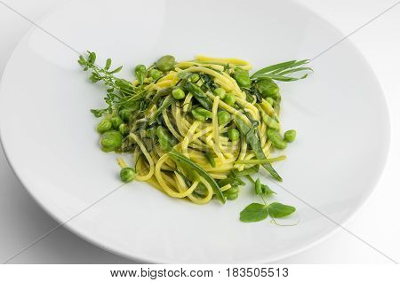 Pasta dish spaghetti with herbs and spring veggies isolated on white